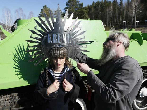 Modelo posa com chapéu de ferro bizarro em frente a monumento de guerra em Krasnoyarsk, na Rússia (Foto: Ilya Naymushin/Reuters)