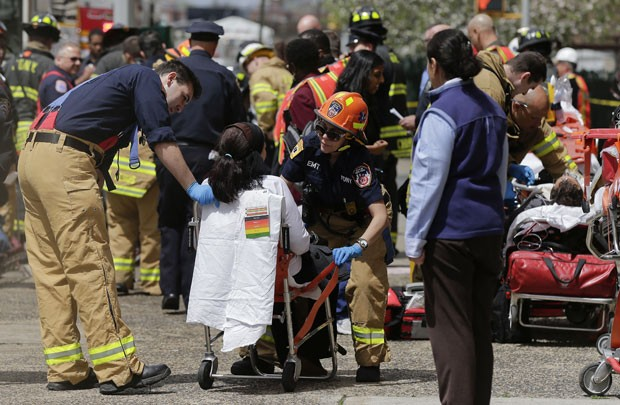 Equipe de bombeiros ajuda mulher que foi retirada do trem que descarrilou no beirro do Queens (Foto: Julie Jacobson/AP)