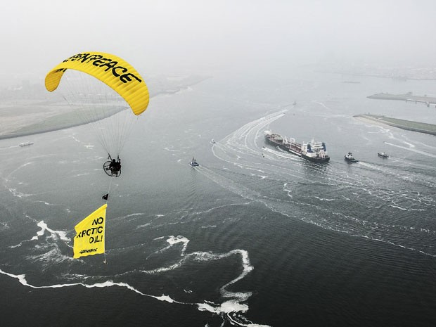 """Imagem disponibilizada pela ONG Greenpeace mostra ambientalista em parapente com faixa escrita """"Não ao óleo ártico"""". Abaixo, é possível ver o cerco de embarcações da ONG ao navio russo com carga de petróleo extraída da região polar (Foto: Ruben Neugebauer, Greenpeace/AP)"""