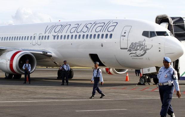 Integrantes da Força Aérea da Indonésia são vistos ao lado do avião da Virgin Australia que sofreu um alerta de tentativa de sequestro nesta sexta-feira 25). Um passageiro bêbado e alterado tentou invadir a cabine do piloto. O avião pousou em segurança e (Foto: Firdia Lisnawati/AP)