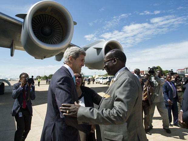 Ministro dos negócios estrangeiros do Sudão do Sul, Barnabé Mariano Benjamin, cumprimenta John Kerry após a sua chegada a bordo de um avião militar dos EUA no Aeroporto Internacional de Juba nesta sexta (2) (Foto: Saul Loeb/ AFP)