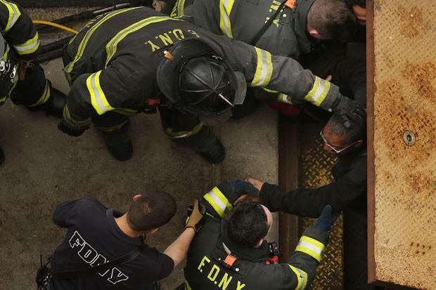 Bombeiros retiram passageiros por uma escada de emergência (Foto: Spwencer Platt/AFP)
