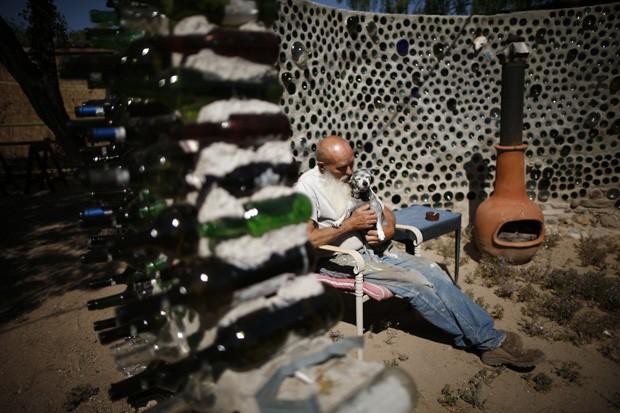 Roy Lohr, de 69 anos, segura seu cachorro dentro de 'nave espacial' feita de garrafas de vinho e cerveja nos EUA (Foto: Lucy Nicholson/Reuters)