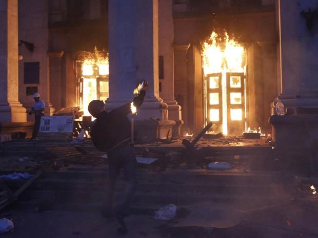 Protestante joga bomba em prédio sindical em Odessa, nesta sexta-feira (Foto: Reuters/Yevgeny Volokin)