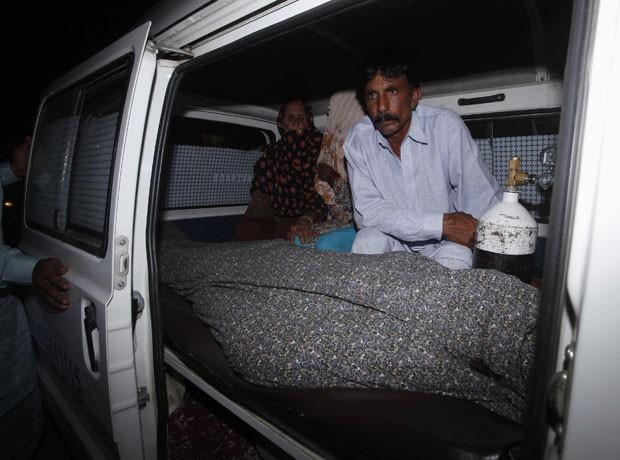 Mohammad Iqbal acompanha o corpo da mulher no necrotério, após ela ser apedrejada por membros da família (Foto: Mohsin Raza/Reuters)