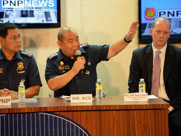 Ao centro, Gilbert Sosa, chefe da polícia filipina da divisão de crimes cibernéticos durante coletiva de imprensa (Foto: Ted Aljibe/ AFP )