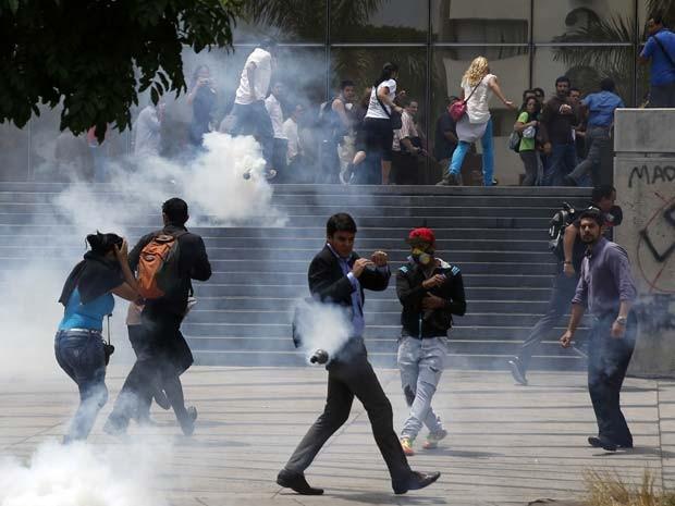 Pessoas fogem de bombas de gás durante protesto contra o presidente Nicolás Maduro em Caracas nesta quinta (8) (Foto: REUTERS/Carlos Garcia Rawlins)