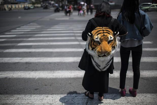 Mulher espera para atravessar cruzamento com mochila em formato de cabeça de tigre realista em Xangai, na China (Foto: Aly Song/Reuters)