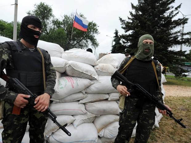 Militantes pró-russos guardam um posto com uma bandeira russa na cidade ucraniana de Donetsk neste sábado (31) (Foto: Viktor Drachev/AFP)
